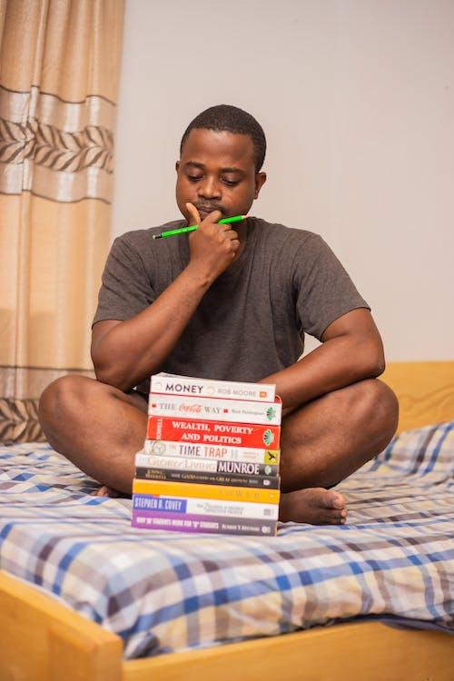 Pensive young black guy doing homework in bedroom