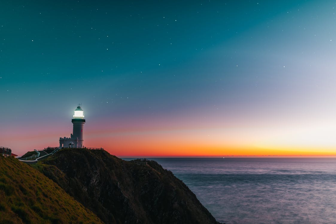Amazing scenery of lighthouse tower located on rocky cliff against starry sunset sky over wavy ocean