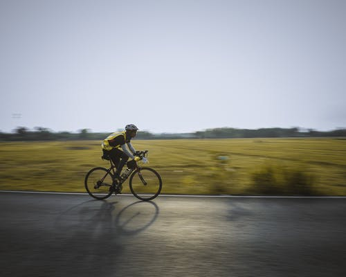Sportsman riding bicycle on road in countryside