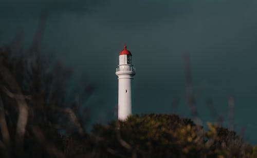 White and Red Lighthouse Under Gray Sky