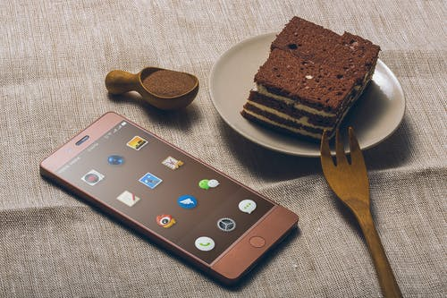 Chocolate Cake on Saucer Beside Iphone