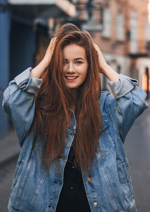 Positive young redhead lady in stylish outfit touching hair and looking at camera while standing on street against blurred buildings
