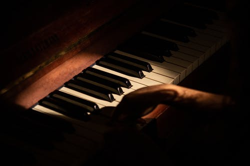 Crop music performer playing piano