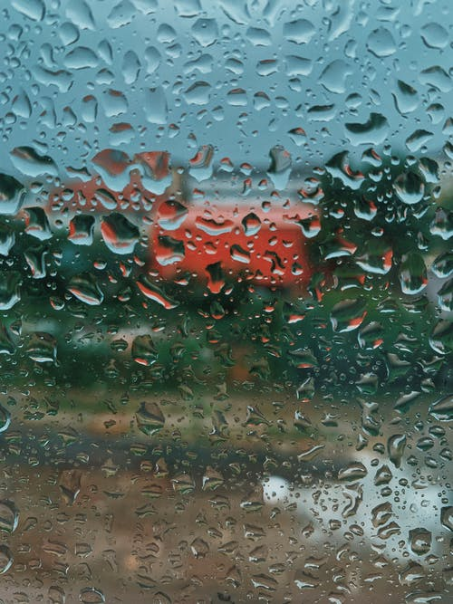 Closeup of glass window with waterdrops with countryside on background on rainy autumn day