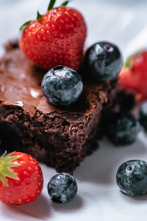 High angle of tasty chocolate cake decorated with strawberries and blueberries on plate