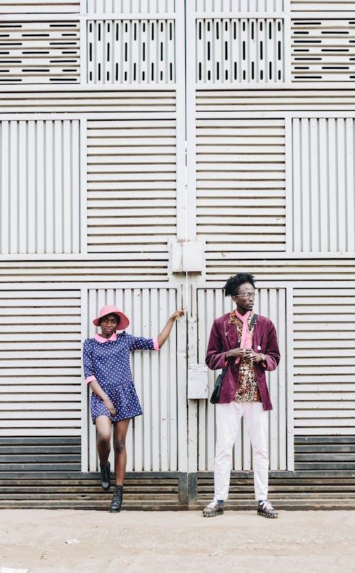 2 Women Standing Beside White Roll Up Door
