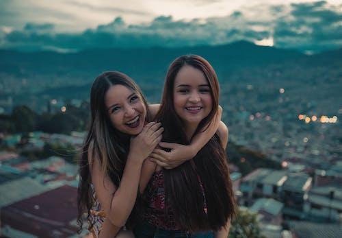 Happy best friends hugging on rooftop