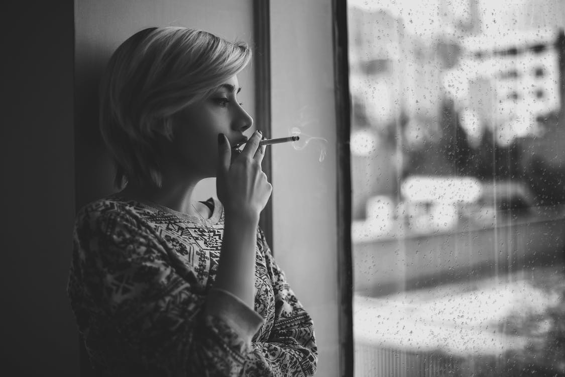Melancholic woman smoking cigarette near window during rain
