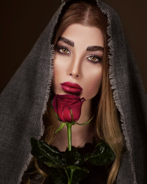 Gorgeous woman under gray cloth with red rose