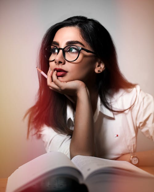 Dreamy woman with book and pencil