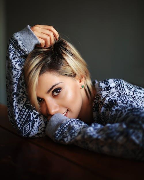 Cheerful woman resting head on arm in dark room