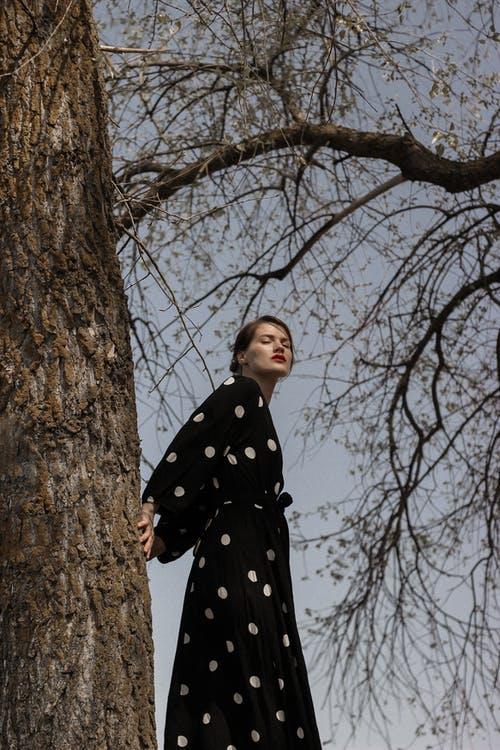 Woman in Black and White Polka Dot Coat Standing Beside Brown Tree