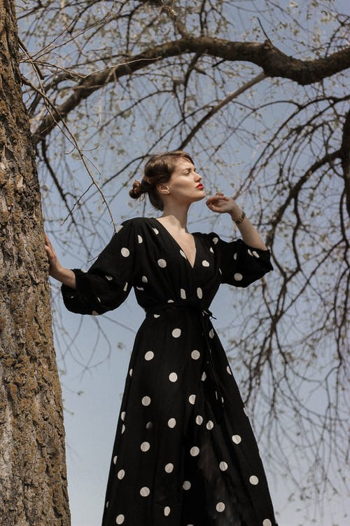 Woman in Black and White Polka Dot Dress Standing Beside Brown Tree