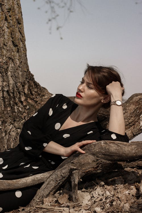 Woman in Black and White Polka Dot Robe Leaning on Brown Rock