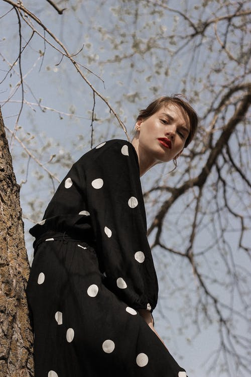 Woman in Black and White Polka Dot Coat Standing Under Leafless Tree