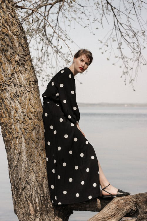 Woman in Black and White Polka Dot Dress Standing Beside Brown Tree Trunk