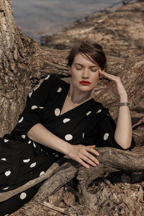 Woman in Black and White Polka Dot Dress Shirt Leaning on Brown Tree