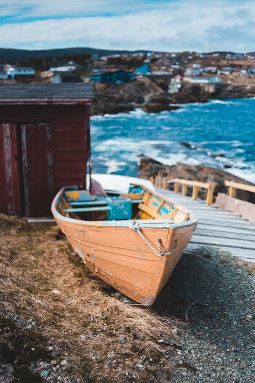Shabby boat with peeled paint placed on gravel ground near wooden pier in village