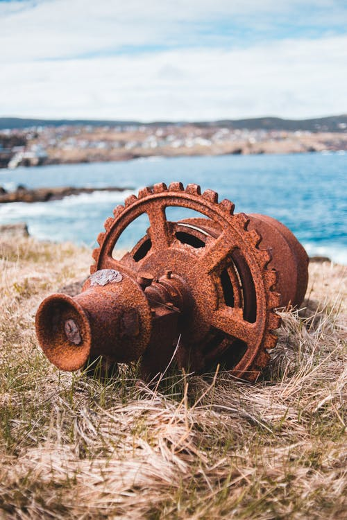 Metal rusted machinery detail left on grassy seashore