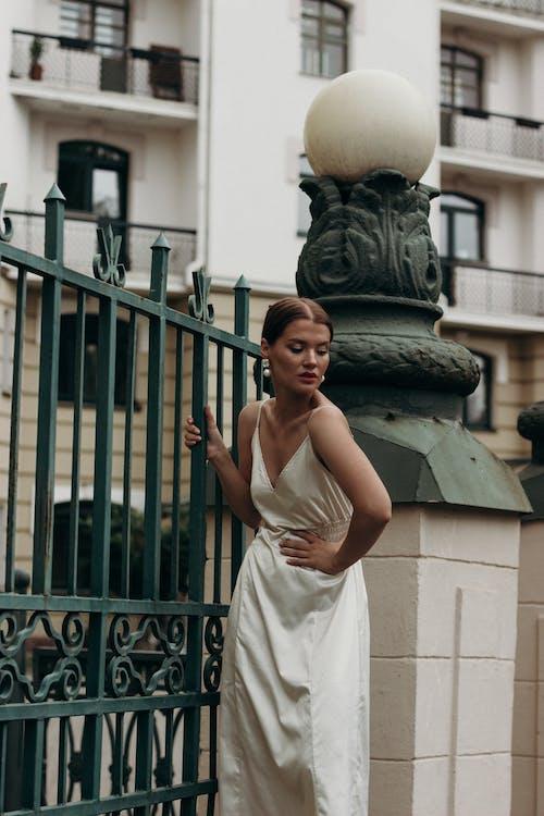 Woman in White Sleeveless Dress Standing Near Black Metal Gate