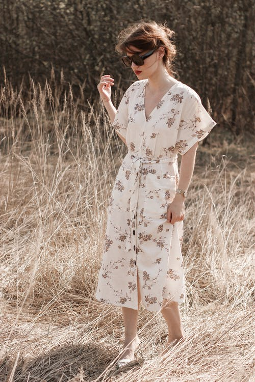 Woman in White and Red Floral Dress Standing on Brown Grass Field