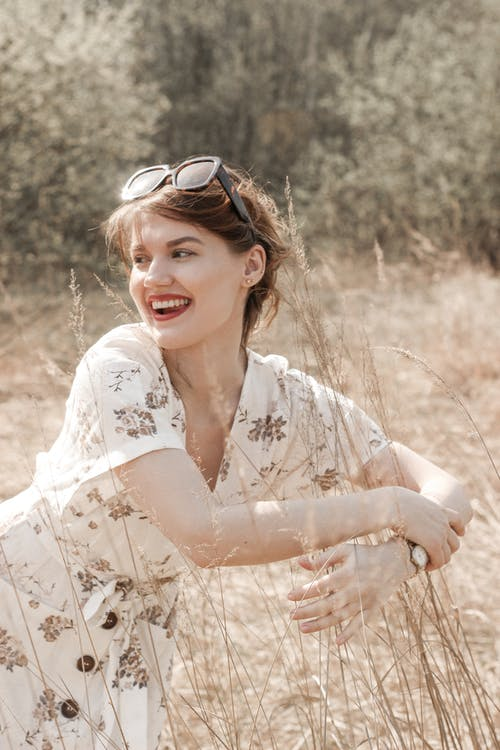 Woman in White and Brown Floral Dress Wearing Sunglasses