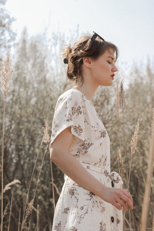 Woman in White Floral Dress Standing on Brown Grass Field