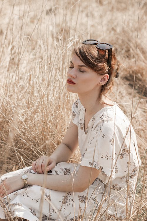 Woman in White Floral Shirt Wearing Black Sunglasses