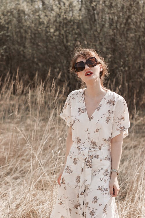 Woman in White Floral Dress Wearing Black Sunglasses Standing on Brown Grass Field