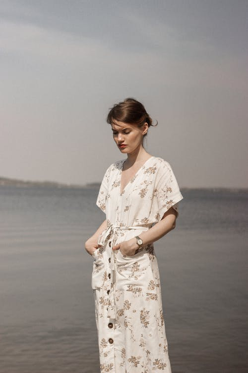 Woman in White and Brown Floral Dress Standing on Beach
