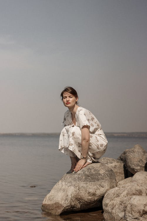 Woman in White and Brown Floral Dress Sitting on Brown Rock Near Body of Water during