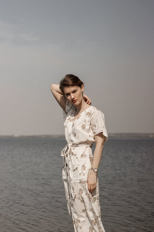 Woman in White and Brown Floral Dress Standing on Seashore