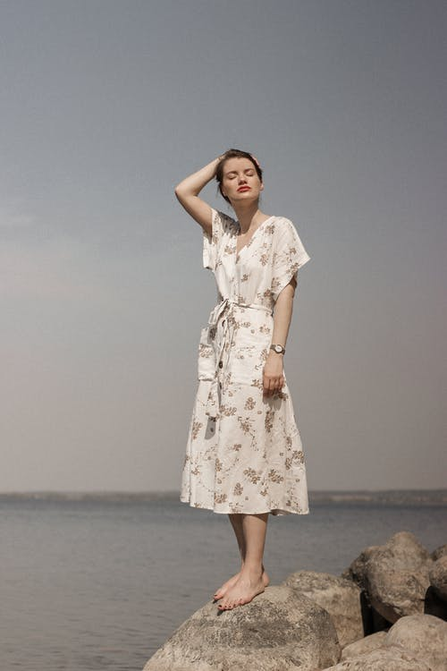Woman in White and Pink Floral Dress Standing on Beach