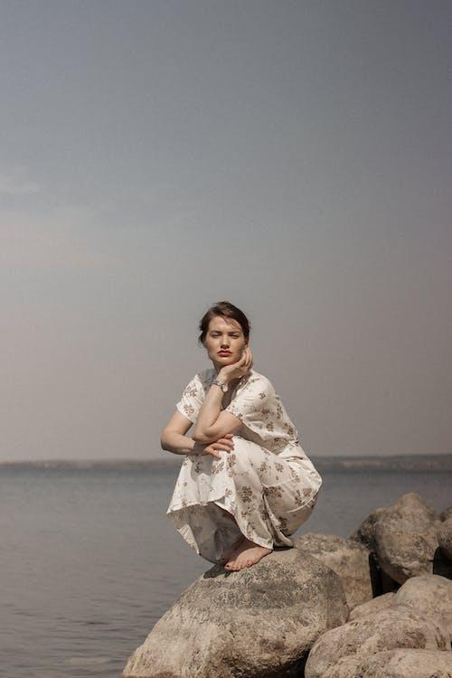 Woman in White Dress Sitting on Rock Near Sea