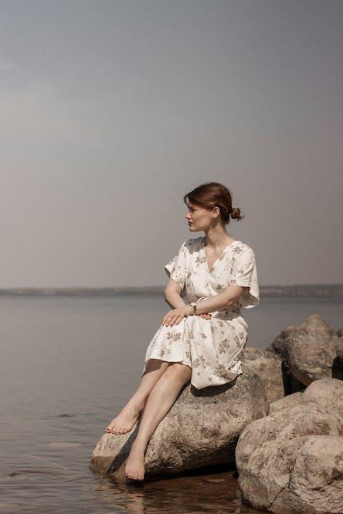 Woman in White Dress Sitting on Rock Near Body of Water
