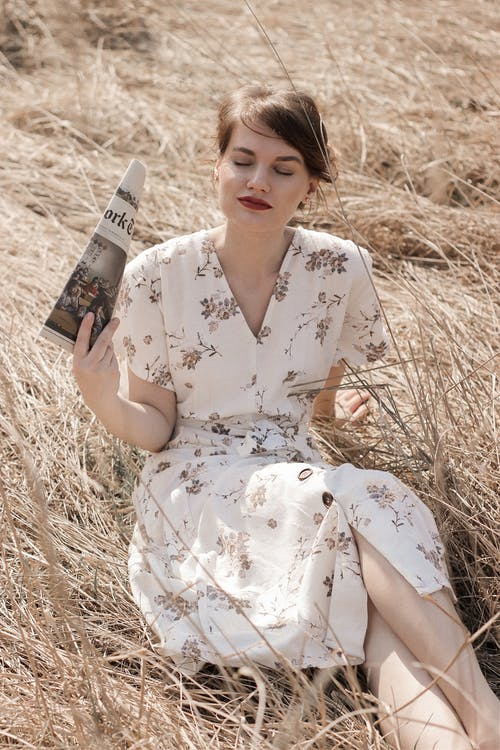 Woman in White and Brown Floral Dress Holding Book
