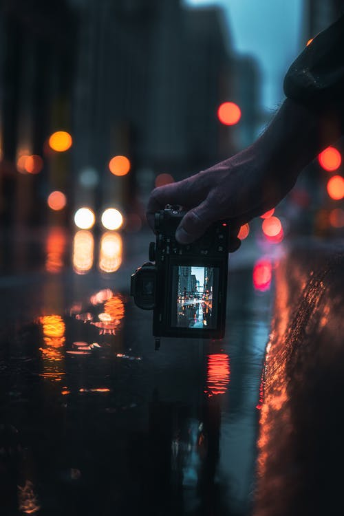 Person Holding Black Dslr Camera Taking Photo of City Lights during Night Time