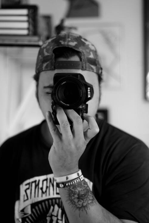 Man in Black Shirt Holding Black Nikon Dslr Camera