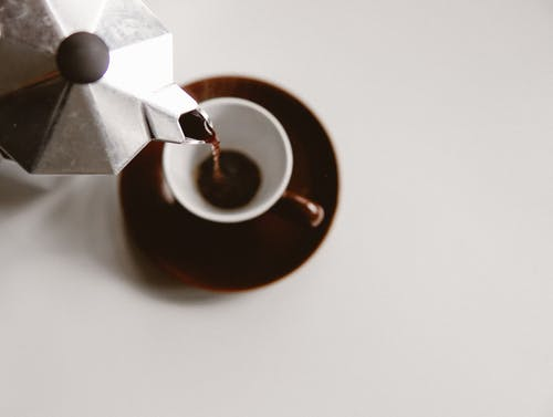 From above of geyser coffee maker pouring freshly brewed beverage into ceramic cup placed on white table