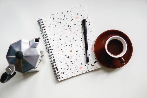 Red and Silver Pen on White Notebook Beside Brown Ceramic Mug