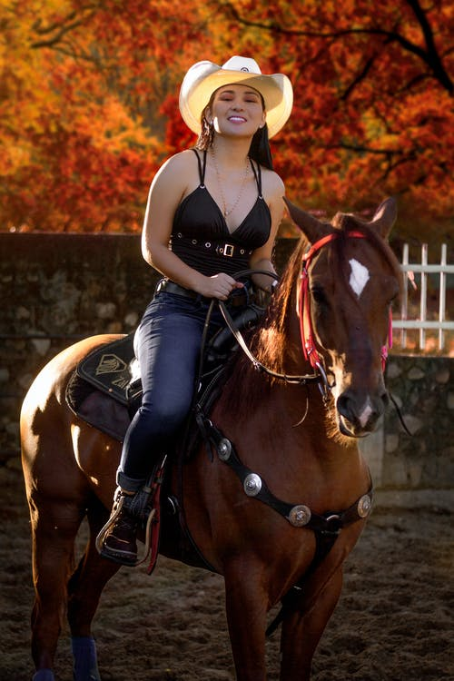 Happy young ethnic woman riding horse in paddock near autumn trees