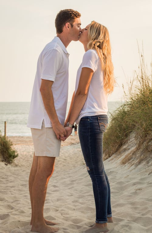 Romantic young couple kissing on sandy beach