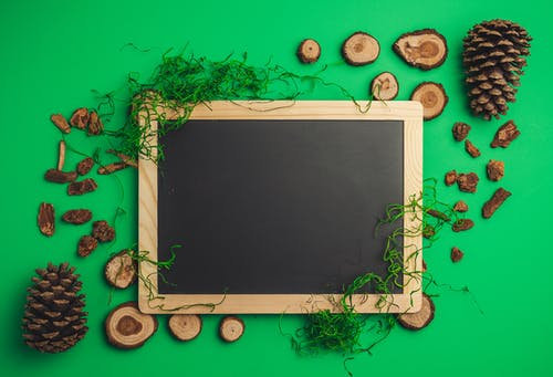Empty chalkboard composed with wooden decorations and cones
