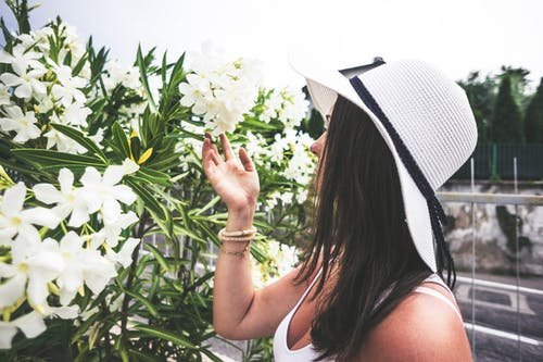 Woman Wearing White Hat Holding White Cluster Flower
