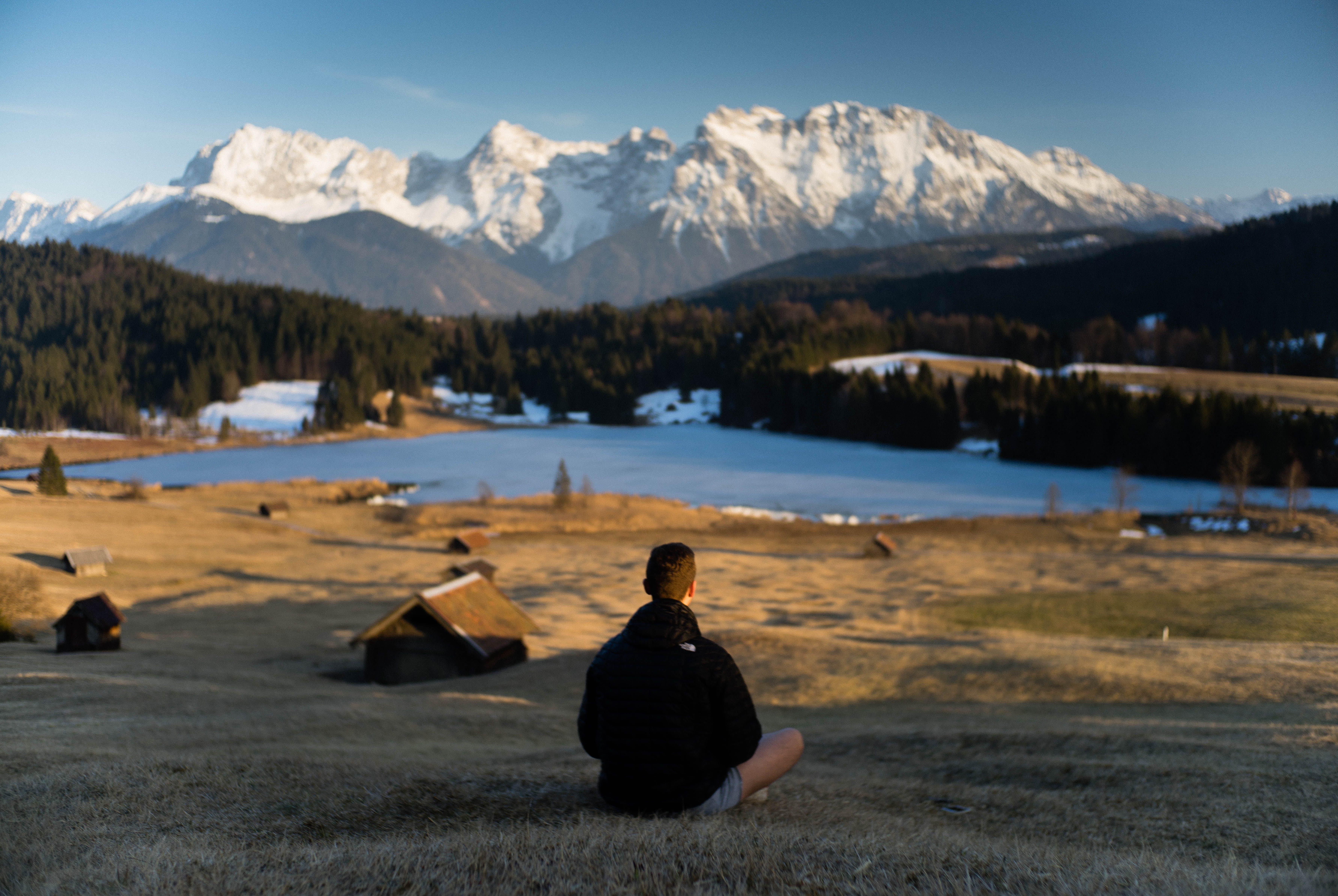 Man Sitting on Green Grass Field