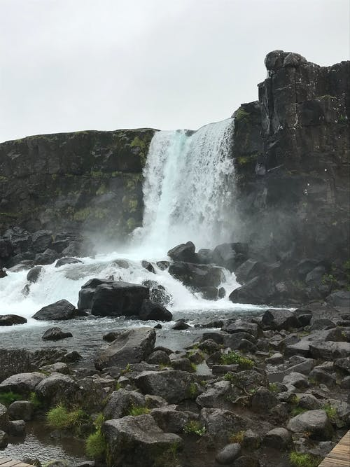 Low angle of powerful waterfall streaming through rocky cliff and flowing into wild river in Thingvellir National Park located in Iceland