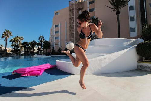 Woman Wearing Black Bikini Playing White Ball Beside Pool