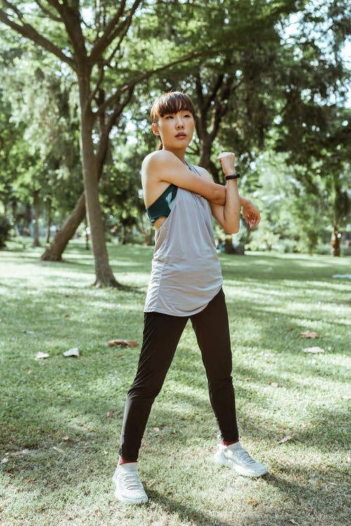 Full length focused adult Asian female athlete in sportswear standing in park while warming up muscles before training alone