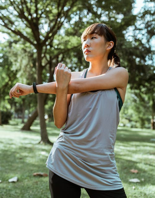Serious Asian sportswoman stretching muscles before workout in nature