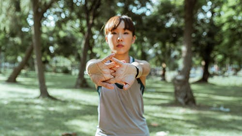 Ethnic sportswoman in activewear standing in park and stretching arms and fingers before training in open air